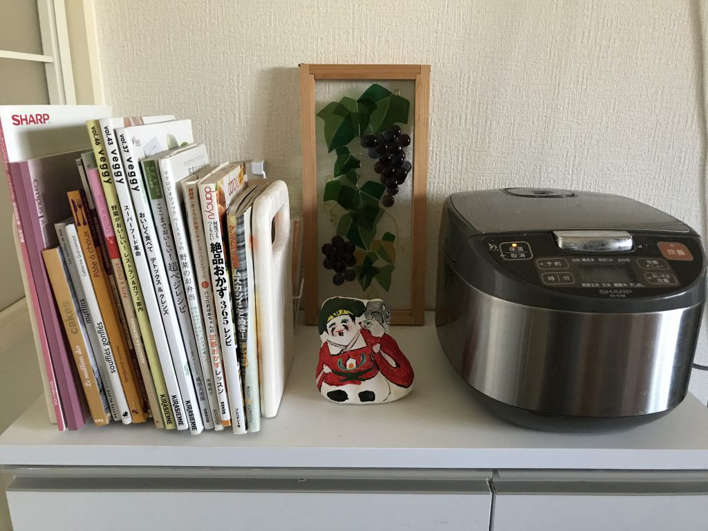 Daikokuten doll standing between recipe books and a rice cooker