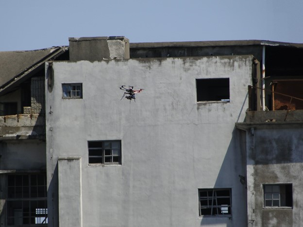 Drone flying in front of a white deserted building