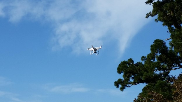 White drone flying in a blue sky