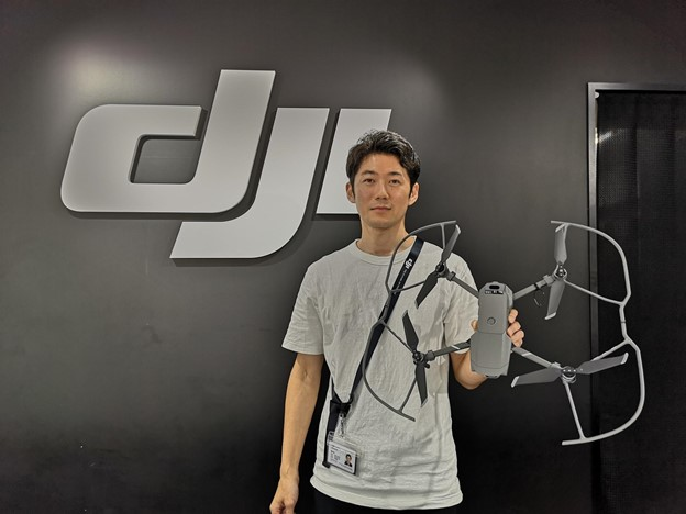Japanese man holding a drone in front of a DJI sign