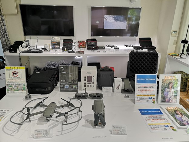 Drones, controllers, cases on display on white tables