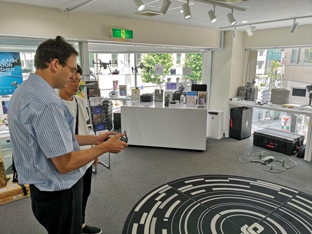David flying a small drone at the DJI store