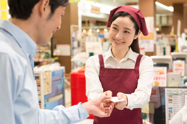 A Japanese supermarket female staff gives a receipt to a male customer