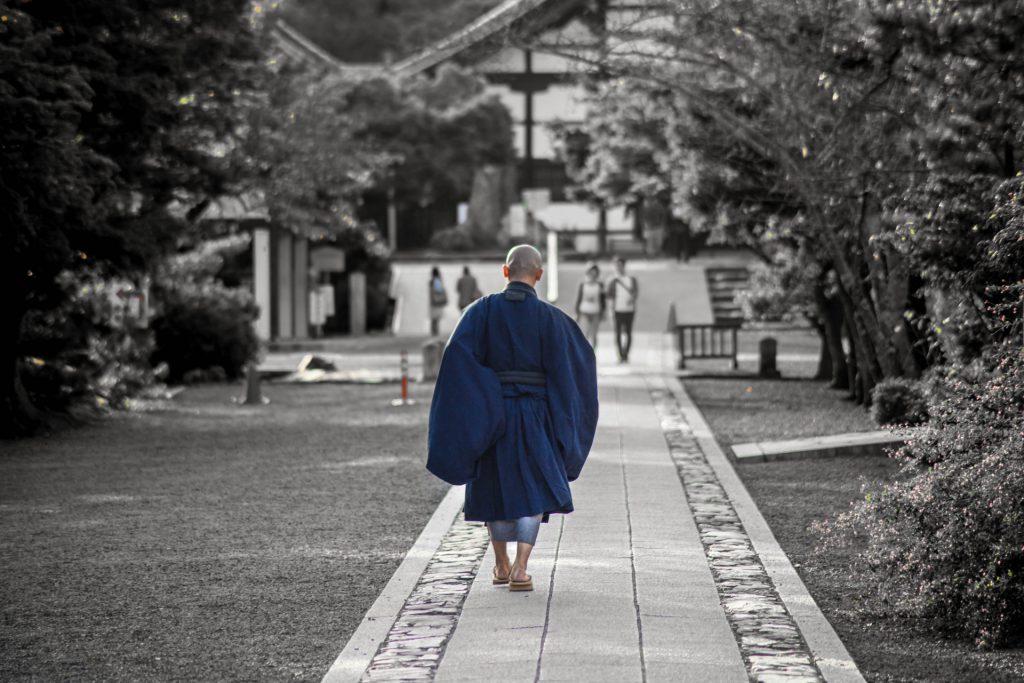 Japanese monk walking near a temple