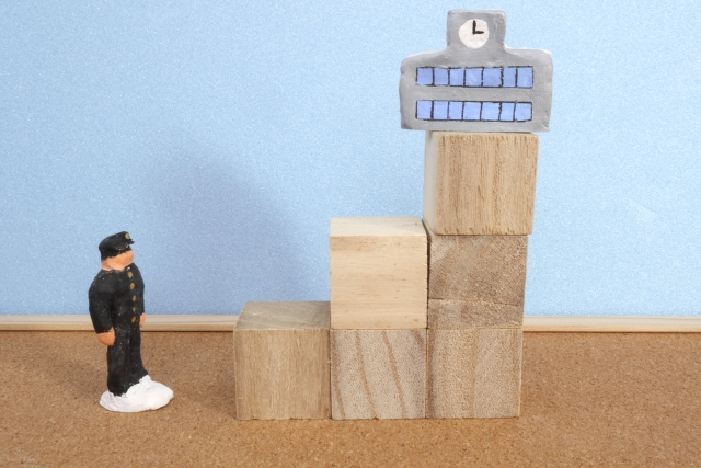 Doll representing a Japanese junior high schooler traying to reach a high school above him on wooden blocks