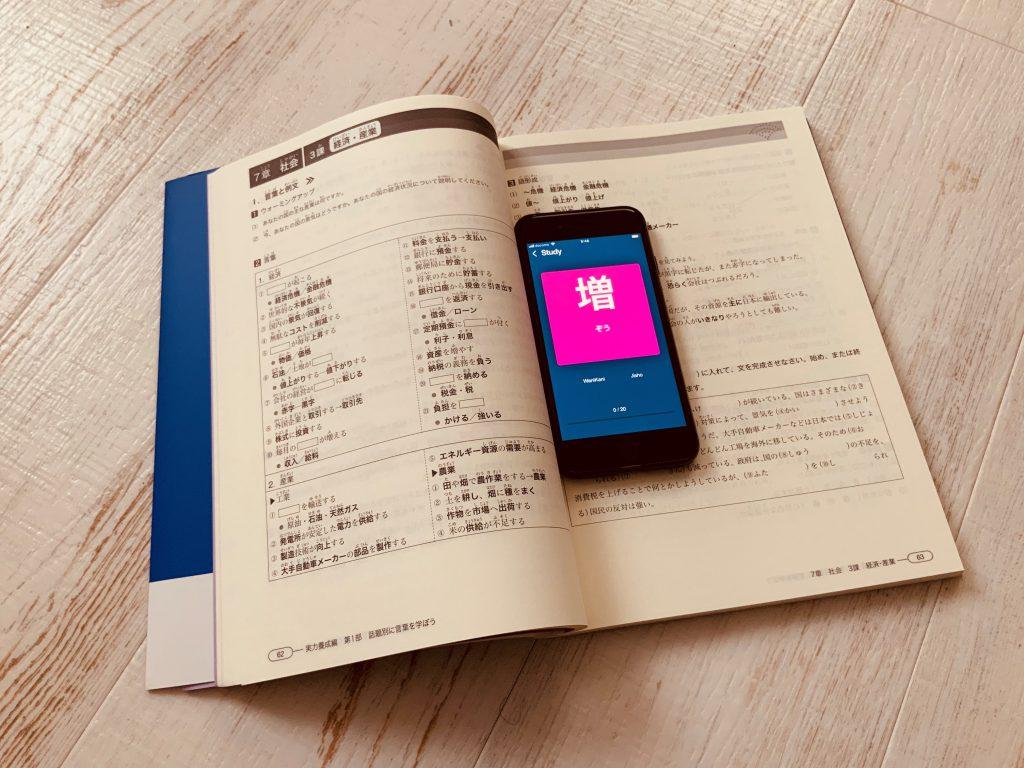 Smarpthone displaying a Japanese language learning app on a Japanese language learning book