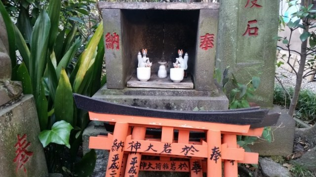 A small altar in which two small white foxes statues can be seen