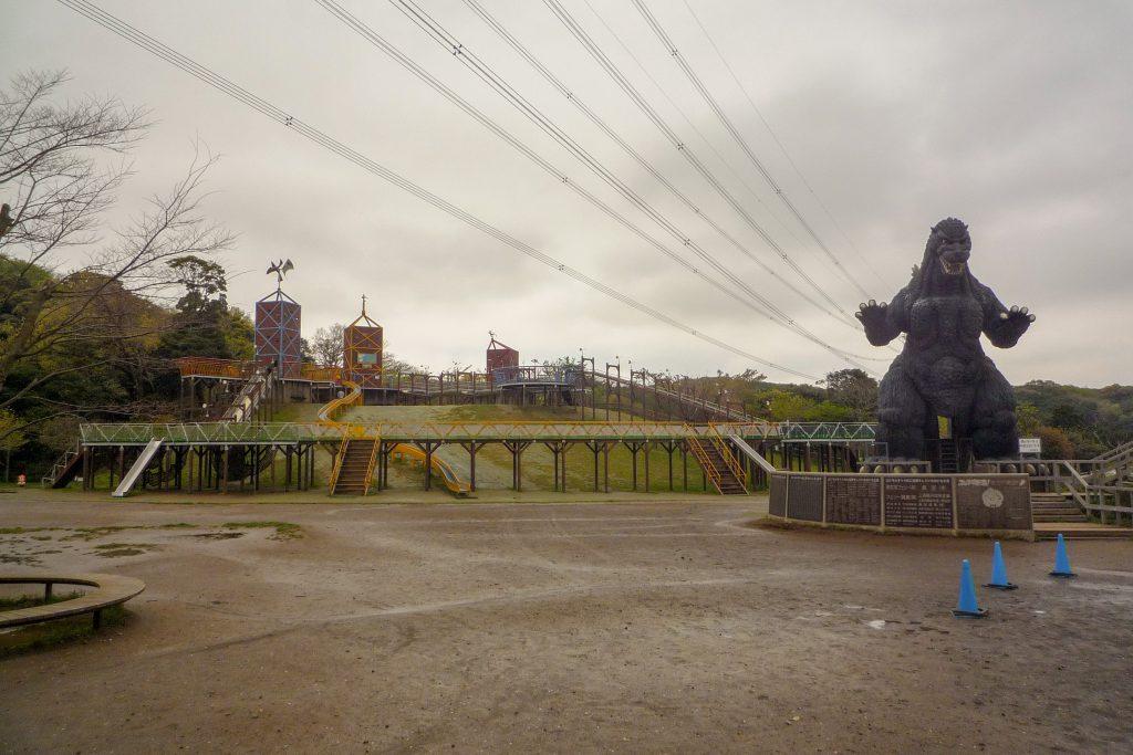 A Godzilla statue in a children's park