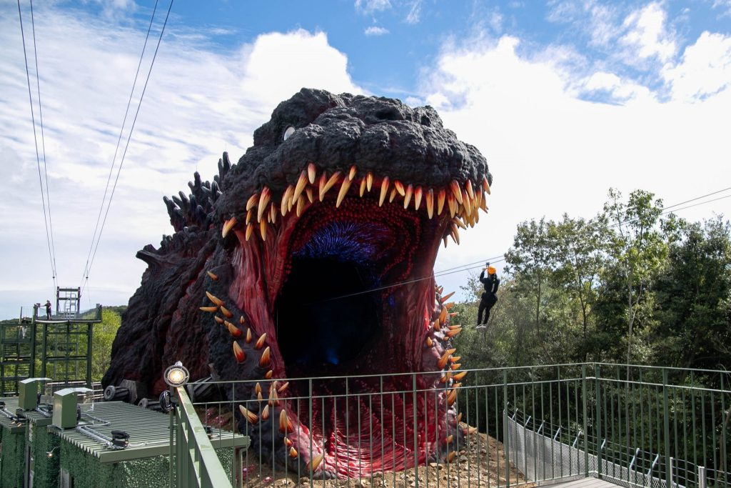 Enormous Godzilla head with its mouth open. Someone on a zip line is about to enter it.