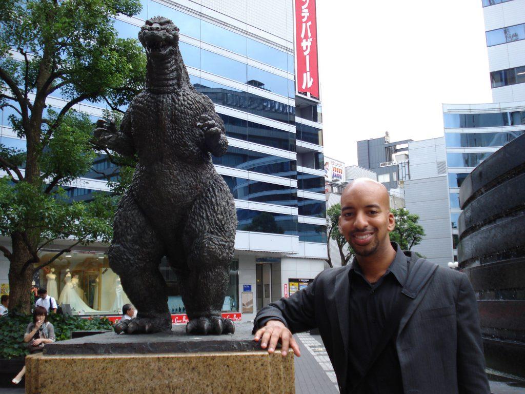 Anthony posing next to a small Godzilla statue
