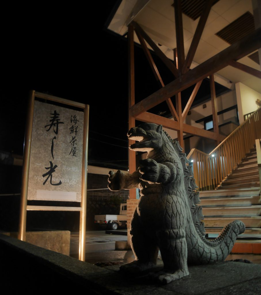 A small Godzilla statue in front of a building