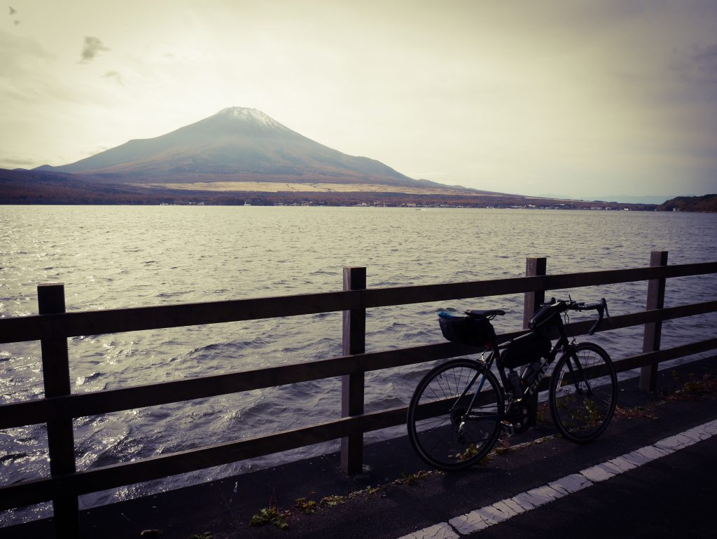 A bicycle rests against a fence along a road. Behind the fence, a lake. On the other side of the shore, far away, is Mount Fuji.
