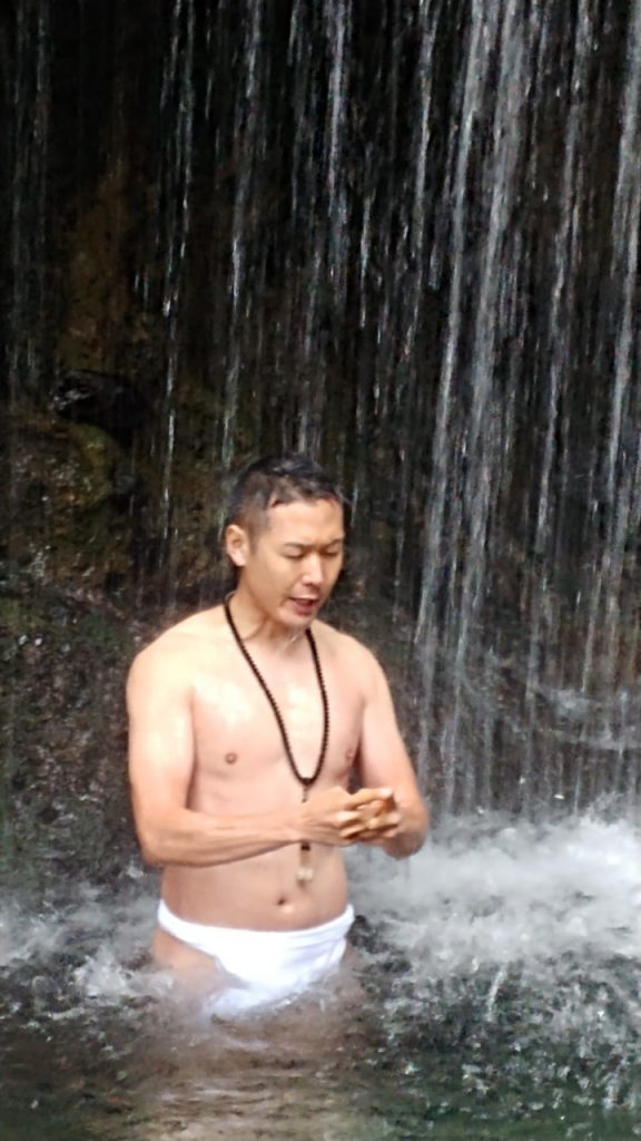 Mr. Tani practicing meditation, hands joined, under a waterfall
