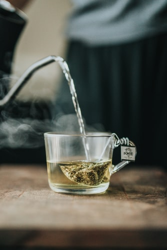 Hot water being poured directly on a  green teabag in a cup