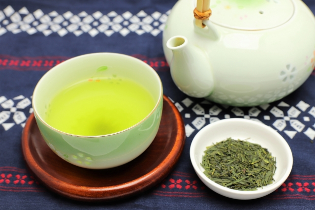 A pot, a cup of green tea and a small plate with green tea leaves