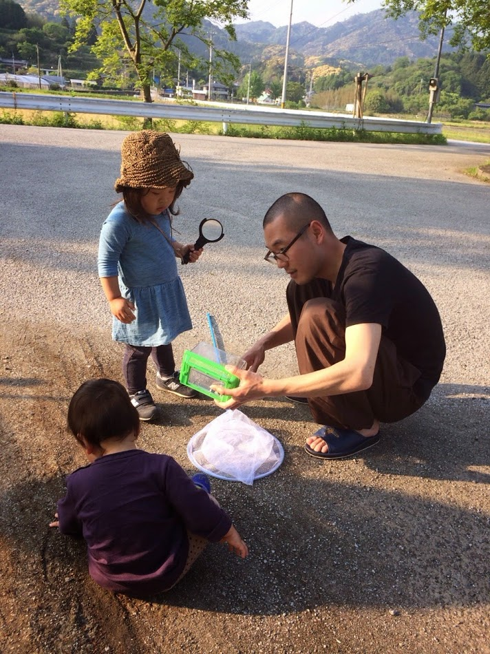A man with a shaved head is playing at catching insects with two small children, a girl and a boy