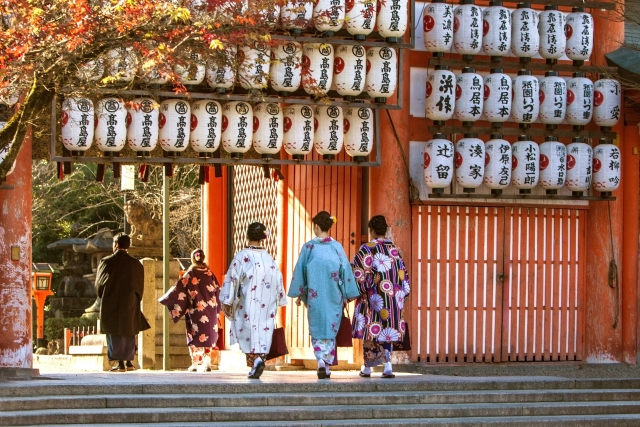 Four women and a man dressed in a kimono enter the gate of a Shinto shrine