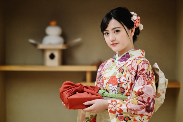 A Japanese woman is dressed in a New Year kimono. A kagami mochi is displayed on a shelf behind her.