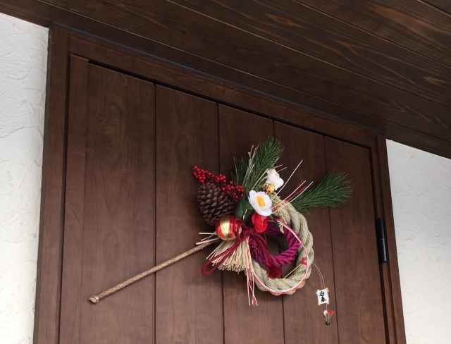 A Japanese traditional decoration made with a sacred cord, floers and pine is displayed on a door