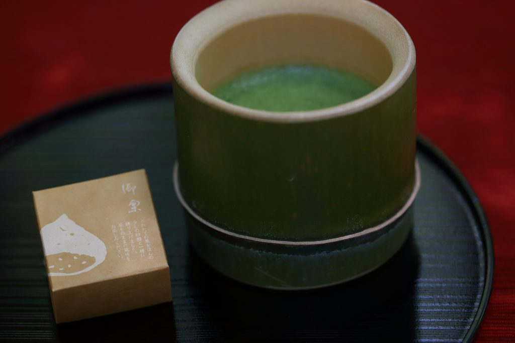 Green tea in a bamboo cup, and a sweet on a plate