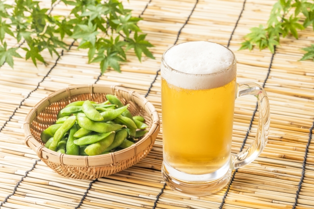 A beer and a small basket in which are soybeans in their green pods
