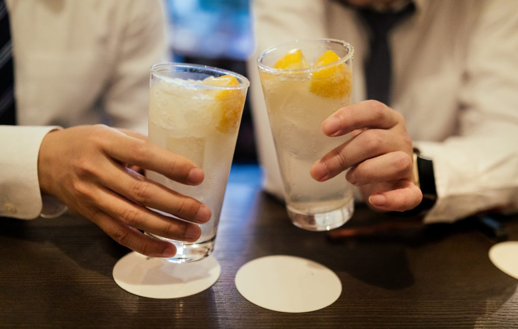 Two people having a toast and holding glasses in which there is a transparent drink with lemon