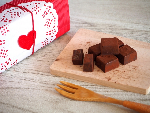 Some chocolates next to a heart-decorated box