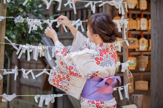 A lady dressed in a kimono is tying an oracle on a thread in a shrine