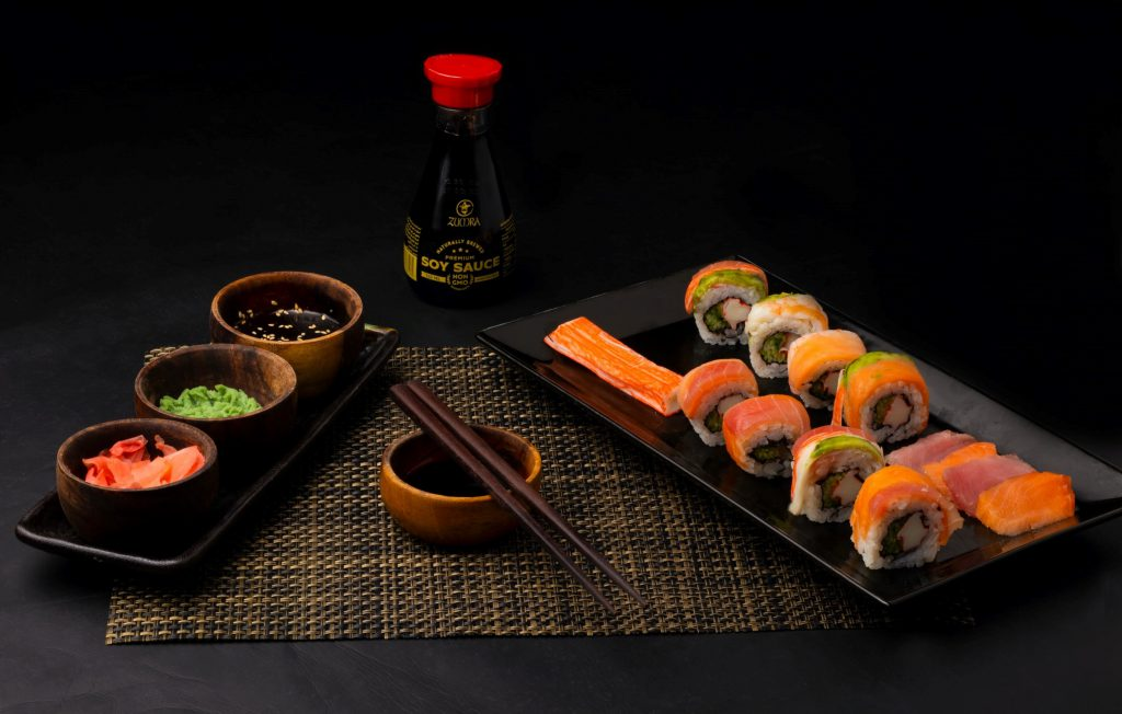 A bottle of soy sauce, sushis and chopsticks