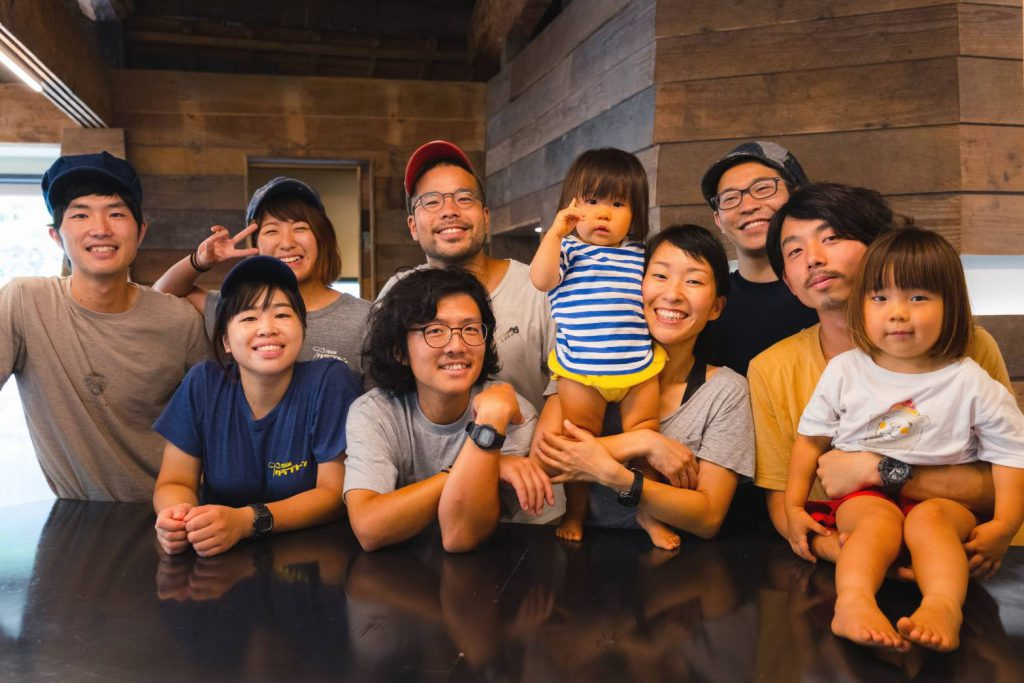 A group of eight adult Japanese people and two kids are smiling at the camera