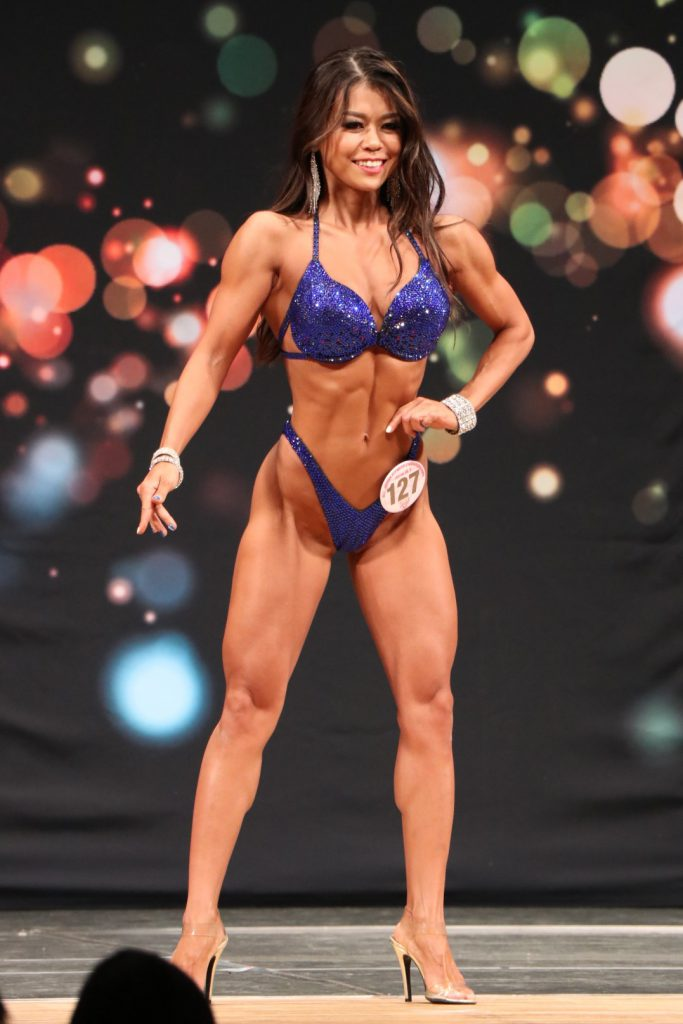 A woman is posing in a swimsuit at a competition