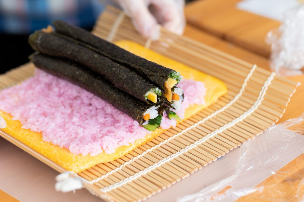 Several thin seaweed sushi rolls are about to be rolled in a bigger sushi