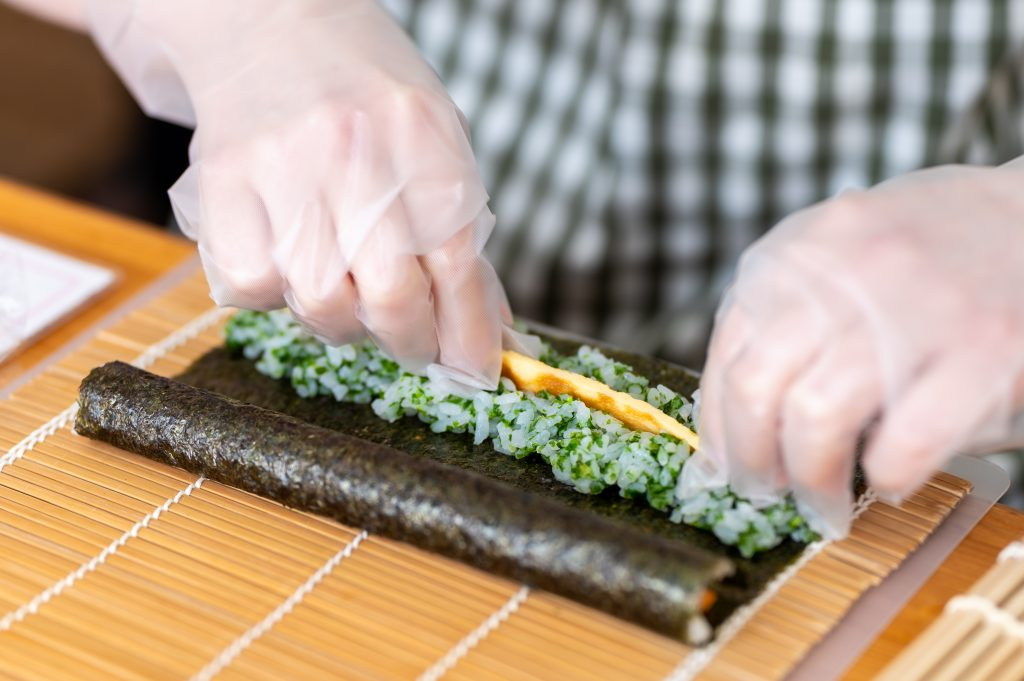 The author is putting rice and other ingredients on wakame seaweed