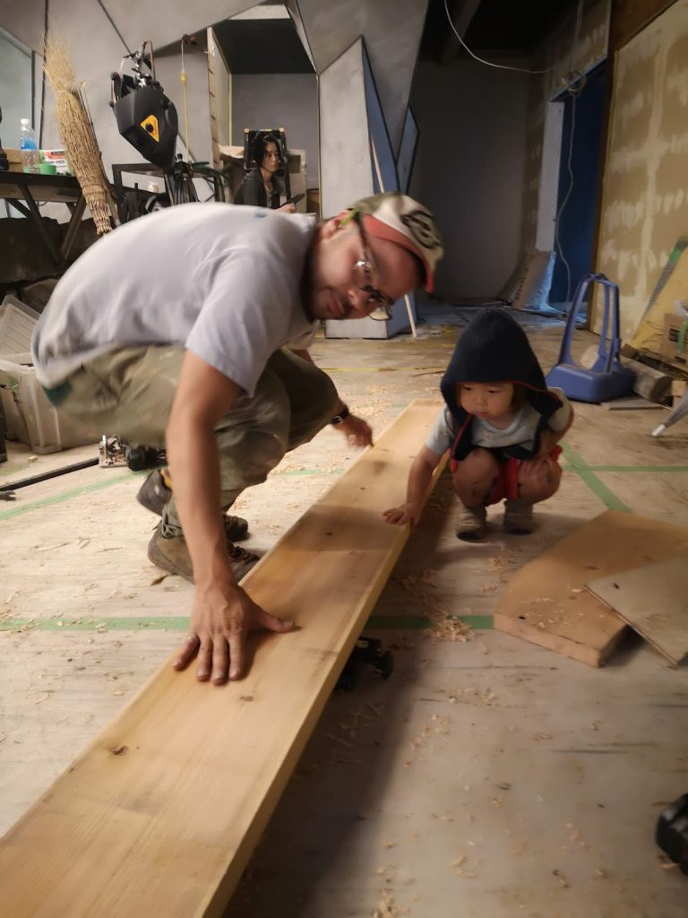 A man and a child touch a wood plank