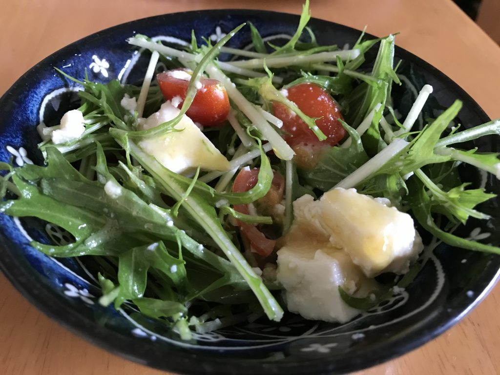 A simple salad with tomatoes, greens and tofu.
