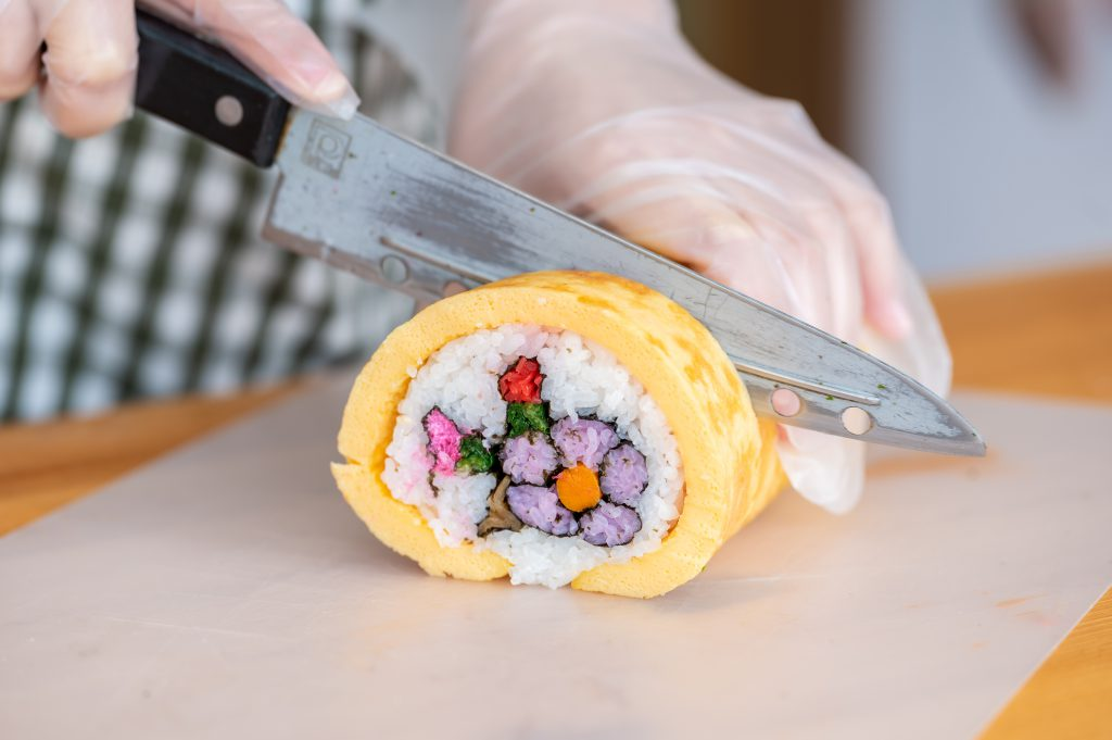 Someone cutting a big sushi roll. the ingredients inside form the shape of a flower
