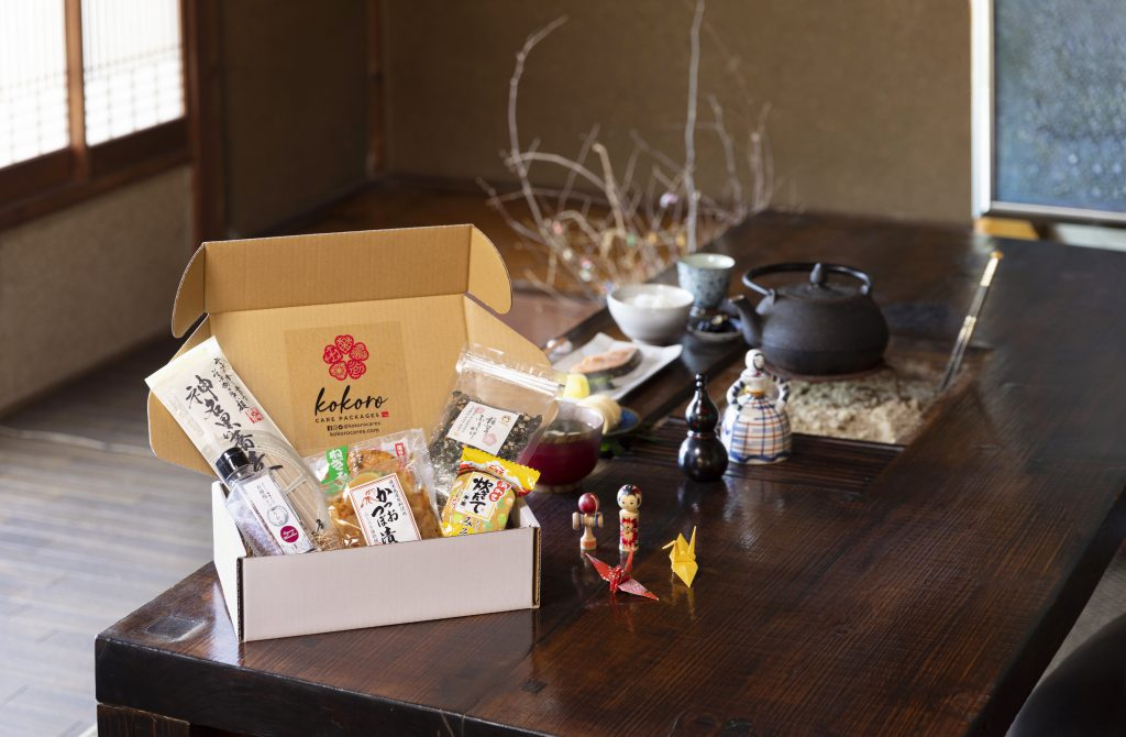 A cardboard box is full with Japanese food packages.