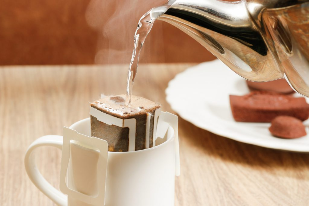 Water is poured on a coffee bag on top of a cup