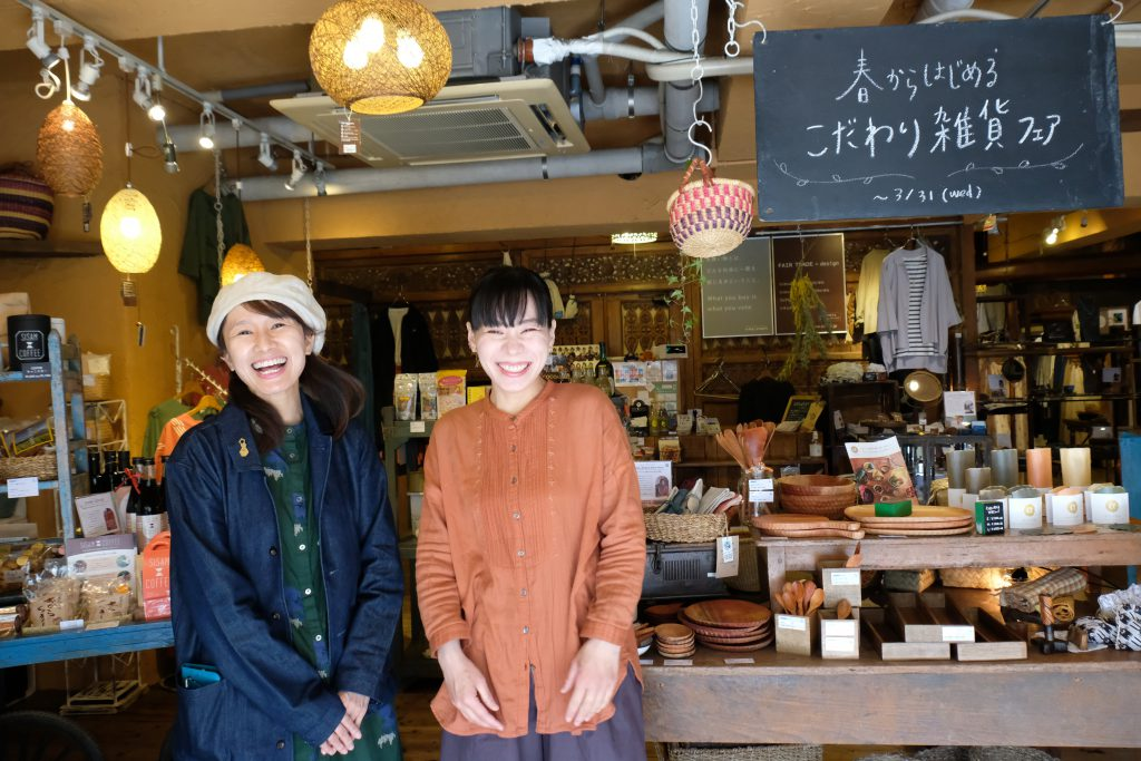 Two Japanese women are smiling in front of a shop
