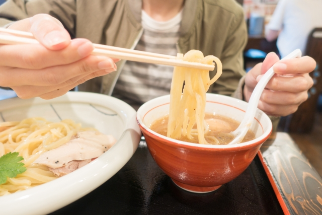 A man is dipping noodles into the soup with chopsticks.