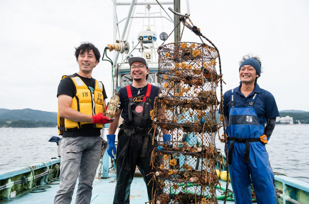 Mr. Sasaki is on a boat with two oyster producers. He is holding a bottle of wine. Next to them, a oyster net.