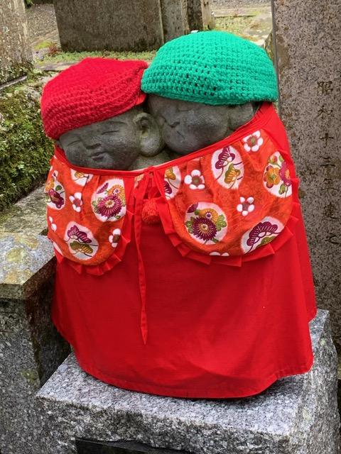 A small statue represents two childish looking figure hugging together. They are covered by a red bib.