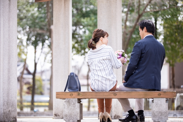 A man and a woman are sitting on a bench. The woman receives flowers from the man.