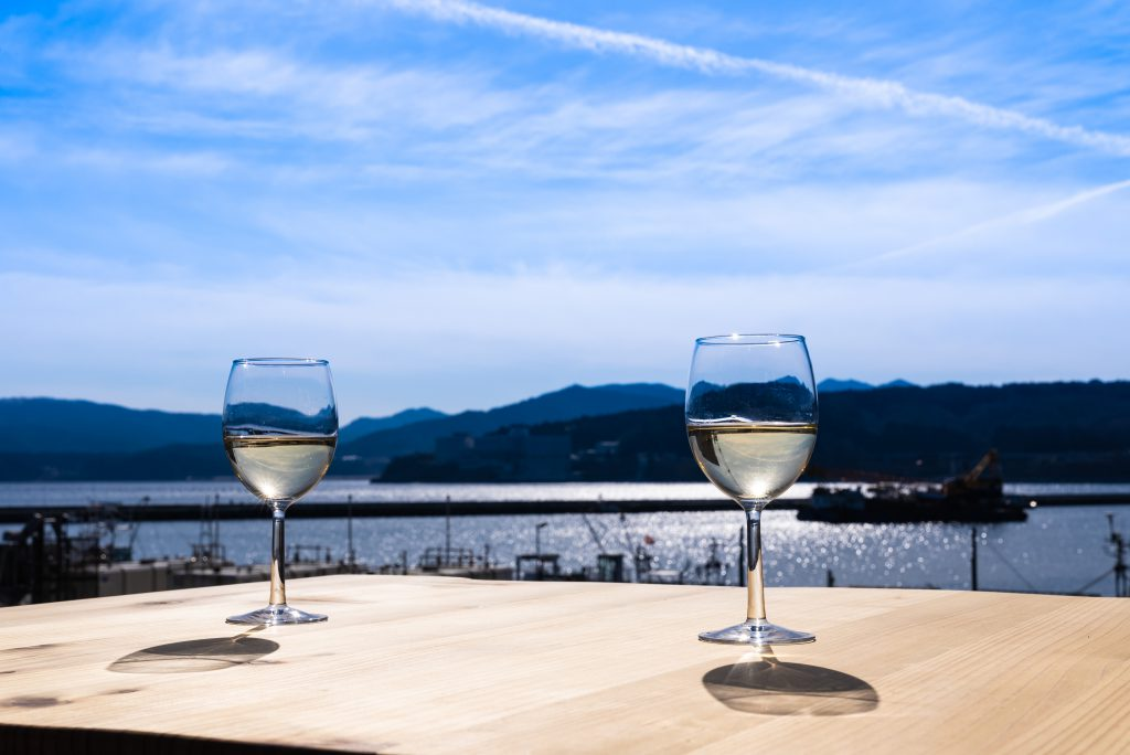 Two glasses of white wine on a table near the sea
