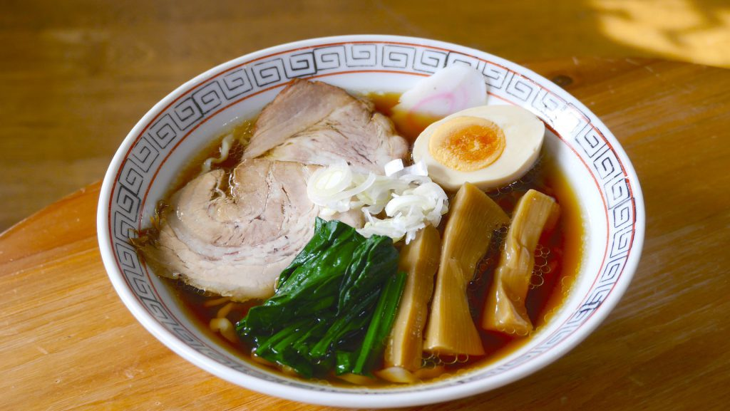 A bowl of noodles in soup with meat, eggs and bamboo shoots