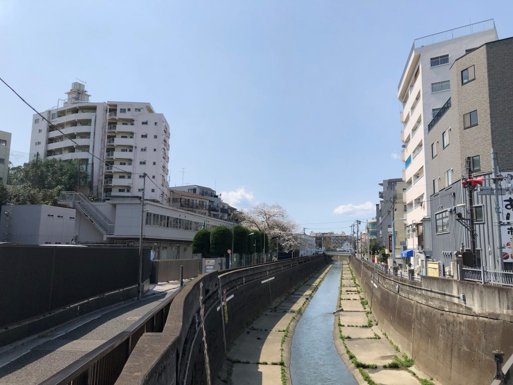 A small river is flowing between buildings