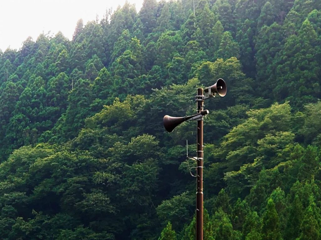 A huge pole with speakers at the top. Behind it, a forest.