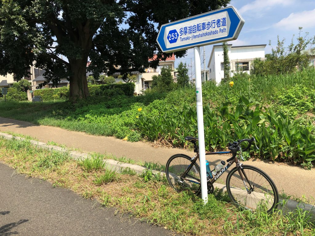 A bicycle is put next to a sign indicating the Tamako cycling road.