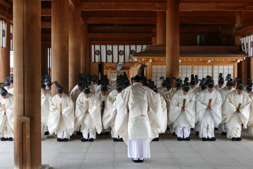 Inside a shrine, many Shinto priests dressed in white attire bow in front of a head priest.