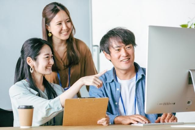 Three young employees looking at a computer screen.